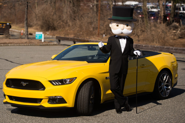 Mr. Monopoly posing with the Ford Mustang