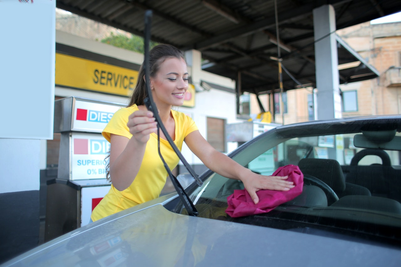 Woman in yellow t-shirt cleaning car